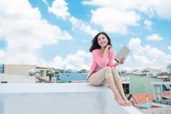 Concetto di libertà godimento Giovane donna asiatica che si rilassa sotto blu immagini stock