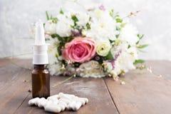 Concetto di malattia del polline con spruzzo, le pillole ed il mazzo dei fiori fotografia stock libera da diritti