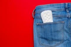 Concetto di mestruazione un cuscinetto mestruale in jeans intasca immagine stock libera da diritti