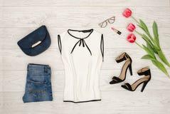 Concetto di modo Blusa bianca, borsa blu, vetri, rossetto, scarpe nere e tulipani rosa Vista superiore, fondo di legno leggero Fotografia Stock