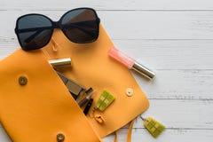 Concetto di modo Cose femminili, prodotti cosmetici, sunglass, orecchini e borsa arancio su fondo di legno con copyspace piano fotografie stock