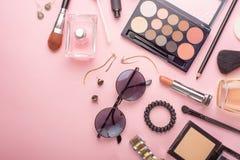 Concetto di modo del blog di bellezza Stile femminile degli accessori: cosmetici, vetri, profumi, ombretti, tush su un fondo rosa fotografia stock libera da diritti