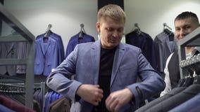 Concetto di modo e di acquisto - rivestimento di scelta e di prova del giovane sopra in centro commerciale o in negozio di vestit stock footage