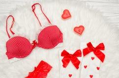Concetto di modo Reggiseno rosso e calze bianche con gli archi, candele sotto forma di un cuore su una pelliccia bianca Vista sup Immagine Stock