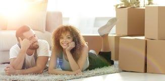Concetto di muoversi verso una nuova casa Coppie felici che si trovano sul pavimento immagini stock