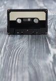 Concetto di musica Audio cassetta nera sui precedenti di legno grigi Fotografia Stock Libera da Diritti