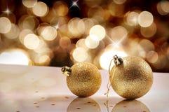 Concetto di Natale con due palle di Natale dell'oro e bokeh dorato Fotografia Stock Libera da Diritti