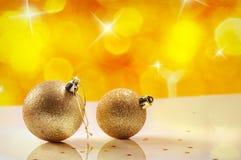 Concetto di Natale con due palle di Natale dell'oro e bokeh giallo Fotografie Stock Libere da Diritti