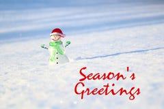 Concetto di Natale Pupazzo di neve di vetro sulla neve, con il saluto della stagione di frase Immagini Stock
