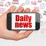 Concetto di notizie: Passi la tenuta dello Smartphone con le notizie quotidiane su esposizione Immagine Stock