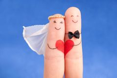Concetto di nozze - persone appena sposate dipinte alle dita contro cielo blu Fotografia Stock