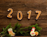 Concetto di nuovo anno Figura 2017 e gallo del pan di zenzero e calzino per i regali, ramo dell'abete su un fondo di legno Fotografie Stock
