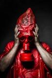 Concetto di orrore, uomo con la maschera antigas rossa. immagini stock