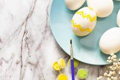 Concetto di Pasqua - disposizione piana del piatto blu con le uova e le pitture variopinte con una spazzola per le uova di vernic immagini stock