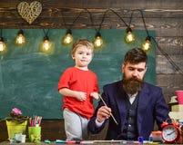 Concetto di paternità L'artista di talento passa il tempo con il figlio L'insegnante con la barba, il padre insegna al piccolo fi fotografia stock