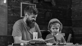 Concetto di paternità Ragazzo, bambino occupato in casco protettivo imparante utilizzare martello con il papà Padre, genitore con fotografia stock libera da diritti