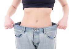 Concetto di perdita di peso - donna esile in grandi jeans isolati su bianco fotografie stock