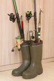 Concetto di pesca: stivali di gomma e canne da pesca Fotografie Stock Libere da Diritti