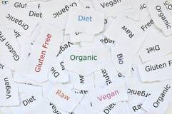 Concetto di piccoli pezzi casuali di carta rotta stampati con le parole organiche, dieta, glutine libero, crudo, bio-, vegano fotografia stock libera da diritti