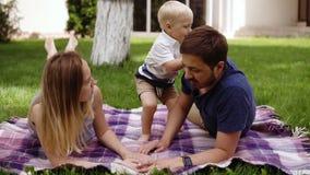 Concetto di picnic della famiglia Giovani genitori che si trovano su un'erba, giocante con suo figlio Diverta Bambino con le sali archivi video