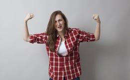 Concetto di potere della ragazza per la risata di giovane castana del muscolo Fotografia Stock