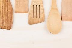 Concetto di progetto del modello dei cucchiai beige di legno vuoti su fondo di legno bianco Fotografia Stock
