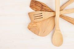 Concetto di progetto del modello dei cucchiai beige di legno vuoti su fondo di legno bianco Immagini Stock