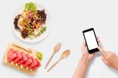 Concetto di progetto del modello facendo uso dello smartphone con insalata, insieme dell'anguria Fotografia Stock Libera da Diritti