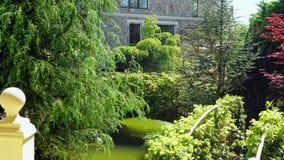 Concetto di progetto del paesaggio Giardino fertile con gli alberi e le piante variopinte nel giorno soleggiato di estate video d archivio