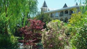 Concetto di progetto del paesaggio Giardino fertile con gli alberi e le piante variopinte nel giorno soleggiato di estate archivi video