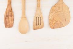 Concetto di progetto di derisione su dei cucchiai beige di legno vuoti su fondo di legno bianco Fotografia Stock