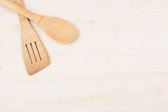 Concetto di progetto di derisione su dei cucchiai beige di legno vuoti su fondo di legno bianco Fotografie Stock