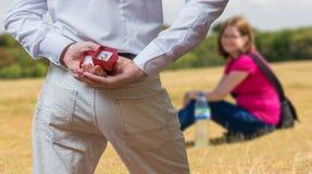 Concetto di proposta di matrimonio L'uomo tiene la fede nuziale dietro indietro immagini stock