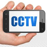Concetto di protezione: Mano che tiene Smartphone con il CCTV su esposizione Fotografie Stock