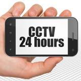 Concetto di protezione: Passi la tenuta dello Smartphone con il CCTV 24 ore su esposizione Fotografia Stock Libera da Diritti