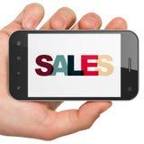 Concetto di pubblicità: Mano che tiene Smartphone con le vendite su esposizione Fotografie Stock Libere da Diritti