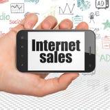 Concetto di pubblicità: Passi la tenuta dello Smartphone con le vendite di Internet su esposizione Immagini Stock Libere da Diritti