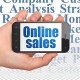Concetto di pubblicità: Passi la tenuta dello Smartphone con le vendite online su esposizione Fotografia Stock