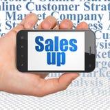 Concetto di pubblicità: Passi la tenuta dello Smartphone con le vendite su su esposizione Fotografia Stock