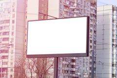 Concetto di pubblicità, tabellone per le affissioni vuoto bianco nella città, costruzioni di appartamento su fondo, spazio della  immagini stock