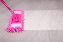 Concetto di pulizia - vicino su della zazzera che pulisce pavimento di legno immagini stock libere da diritti