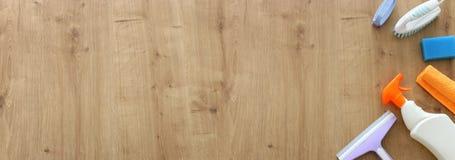 Concetto di pulizie di primavera con i rifornimenti sopra fondo di legno Vista superiore, disposizione piana fotografia stock