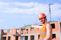Concetto di responsabilità dell'appaltatore Supporto protettivo del casco del tipo davanti a costruzione fatta dai mattoni contro fotografia stock