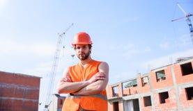 Concetto di responsabilità dell'appaltatore Tipo nel supporto protettivo del casco davanti a costruzione fatta dai mattoni rossi  fotografia stock libera da diritti