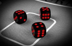 concetto di rischio - giocare i dadi su una tavola di gioco verde Giocando con i dadi Rotoli rossi dei dadi del casinò Rotolament Fotografia Stock