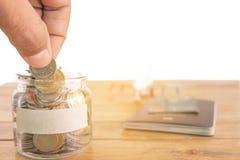 Concetto di risparmio dei soldi Raccolta dei soldi nel barattolo dei soldi per il vostro concetto moneta della tenuta della mano, immagini stock