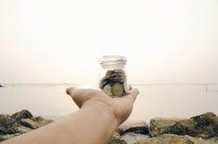 Concetto di risparmio di immagine mano potata che giudica barattolo di vetro contenuto con la moneta fotografie stock libere da diritti