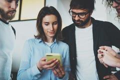 Concetto di riunione d'affari dei colleghe Giovane gruppo facendo uso del dispositivo mobile all'ufficio moderno immagine stock libera da diritti