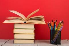 concetto di saggezza e di istruzione - libro aperto sulla tavola di legno, fondo di colore Immagine Stock