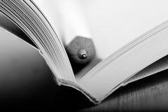 Concetto di saggezza e di istruzione - macro vista del libro con la matita immagine stock